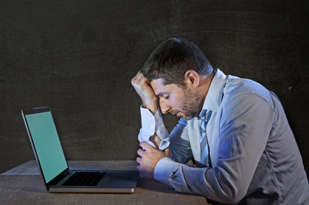 young stressed businessman working on desk with computer laptop thinking and looking sad and frustrated in depression and work problems concept isolated on black grunge background