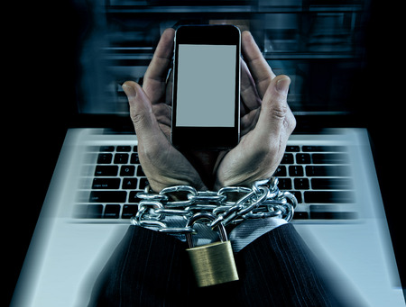 Hands of caucasian businessman addicted to mobile phone bond and locked with iron chain wrists in smartphone internet addiction and slave to online network addict concept