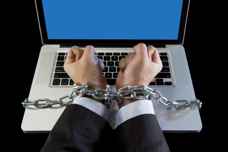 work addicted: Hands of caucasian businessman addicted to work tied and bond with iron chain handcuffed to computer laptop in workaholic, internet slave and addict concept