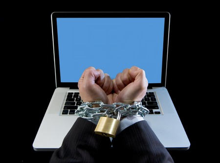 Hands of caucasian businessman addicted to work bond and locked with iron chain handcuffed to computer laptop in workaholic, internet slave and addict concept Stock Photo