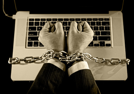 work addicted: Hands of caucasian businessman addicted to work tied and bond with iron chain handcuffed to computer laptop in workaholic, internet slave and addict concept in black and white