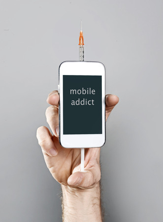 cell phone addiction: hand of internet cellphone addict man holding mobile phone with syringe as  heroin junkie in on line communication and telephone dependency, obsession and addiction concept