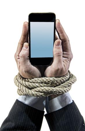 Handen van zakenman verslaafd aan mobiele telefoon touw bond polsen in smartphone internet verslaving en slaaf van online netwerk verslaafde concept geïsoleerd zwarte achtergrond