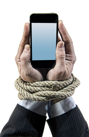 cell phone addiction: Hands of businessman addicted to mobile phone rope bond wrists in smartphone internet addiction and slave to online network addict concept isolated black background Stock Photo
