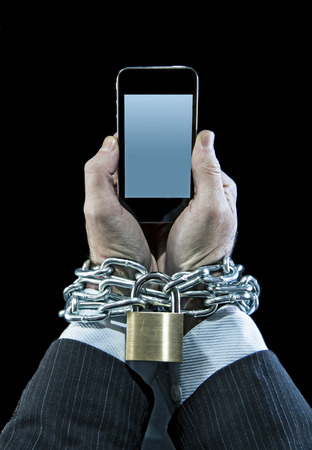 locked in: Hands of businessman addicted to mobile phone chain locked wrists in smartphone internet addiction and slave to online network addict concept isolated black background Stock Photo