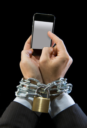 Hands of businessman addicted to mobile phone chain locked wrists in smartphone internet addiction and slave to online network addict concept isolated black background Stock Photo