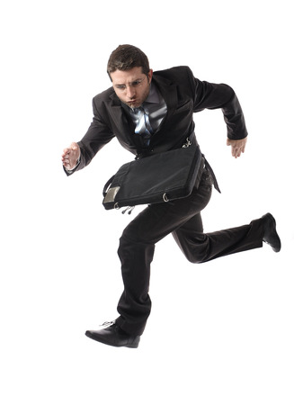 overwork: young attractive businessman in athletic pose running late to work wearing suit and tie in stress and overwork or fast success concept isolated on white background