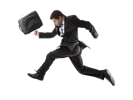 running late: young attractive businessman in athletic pose running late to work wearing briefcase, suit and tie in stress and overwork or fast success concept isolated on white background