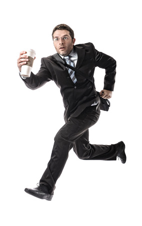 overwork: young attractive businessman with take away coffee running late to work wearing suit and tie hurry up to office in stress and overwork concept isolated on white background