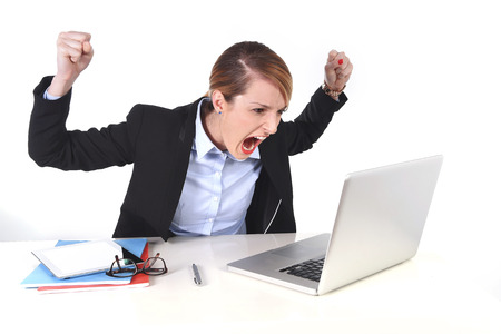 unhappy worker: young attractive businesswoman frustrated and desperate expression at office working on computer laptop in stress at work concept screaming angry isolated on white background