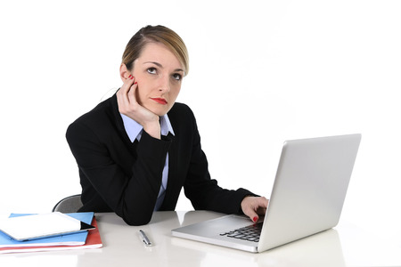 young attractive blond businesswoman thinking and looking thoughtful, pensive and using imagination distraught while working on computer laptop at office desk photo