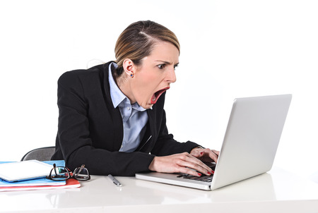 attractive white blond businesswoman sitting at office desk working with laptop in stress looking upset and dealing work issues screaming shouting at computer Stock Photo