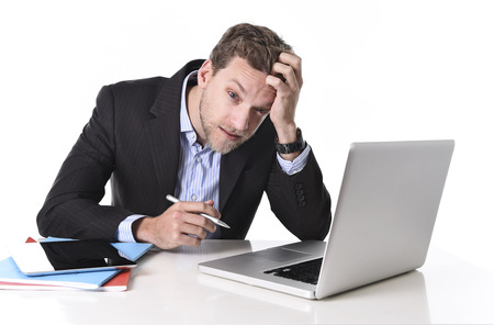 young attractive European businessman working in stress at office desk computer laptop suffering headache, worried and frustrated isolated on white background Stock Photo
