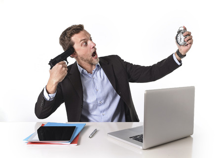 overwork: young attractive European businessman working in stress at office desk computer pointing gun to head holding watch in overwork and overtime work concept