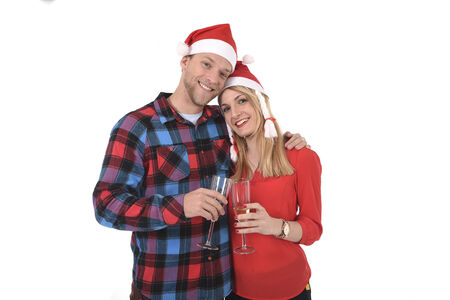Christmas young beautiful couple in Santa hats in love smiling happy together Champagne glasses toast wearing trendy clothes isolated on white background photo