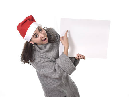 young attractive Hispanic woman wearing Santa Claus Christmas hat and winter jumper holding and pointing blank billboard or placard sign as copy space adding corporate marketing isolated on white background photo