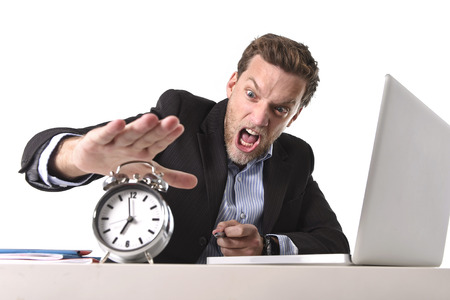 project deadline: young angry exploited businessman at office desk stressed and frustrated with computer laptop and alarm clock in out of time, project deadline, stress and overwork concept