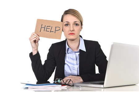 exploited: young attractive frustrated and tired businesswoman holding help sign message overworked at office computer, exhausted, sad under pressure and stress isolated on white Stock Photo