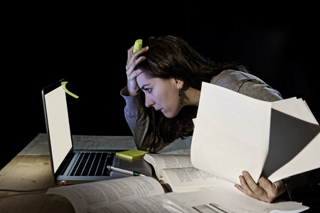 girl studying: young desperate university student girl in stress before exam studying and working with books and computer late night overwhelmed in technology and education concept Stock Photo