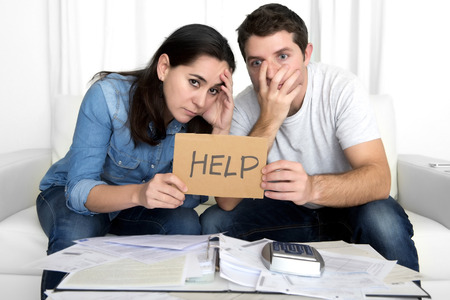 contabilidad financiera cuentas: joven pareja necesitan ayuda preocupado en el estr�s en el sof� en casa papeles bancarios facturas de deuda contable gastos y pagos que sienten desesperados en mala situaci�n financiera Foto de archivo