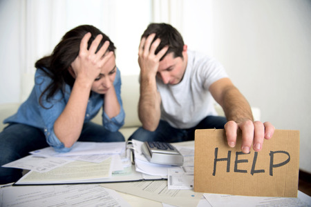 credit card bills: young couple worried need help in stress at home couch accounting debt bills bank papers expenses and payments feeling desperate in bad financial situation