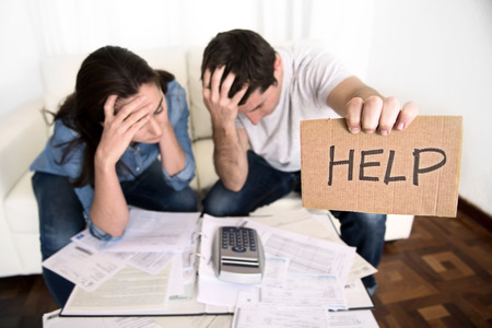 pay bills: young couple worried need help in stress at home couch accounting debt bills bank papers expenses and payments feeling desperate in bad financial situation