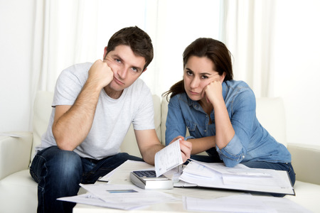 credit crunch: young couple worried home in stress sitting at living room couch accounting debt bills bank papers expenses and payments feeling desperate in bad financial situation