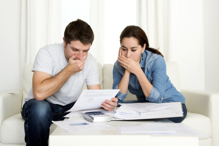 credit card bills: young couple worried home in stress sitting at living room couch accounting debt bills bank papers expenses and payments feeling desperate in bad financial situation