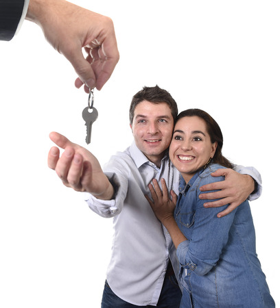 real state: young happy couple receiving the house key of their new flat or apartment in residence moving, home property and real state concept isolated on white background Stock Photo