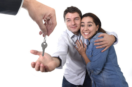 accommodation broker: young happy couple receiving the house key of their new flat or apartment in residence moving, home property and real state concept isolated on white background Stock Photo