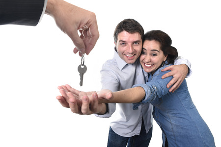 estate: young happy couple receiving the house key of their new flat or apartment in residence moving, home property and real state concept isolated on white background Stock Photo