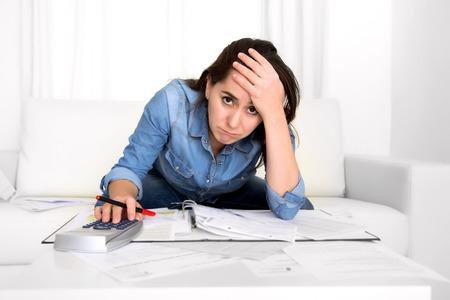 jonge vrouw ongerust thuis in stress op woonkamer boekhoudkundige schuld rekeningen kosten met rekenmachine gevoel wanhopig op betalingen in slechte financiële situatie begrip Stockfoto