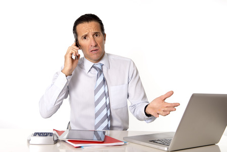 angry businessman: angry senior businessman in stress working and talking on mobile phone at office desk looking desperate and worried for financial crisisl isolated on white background