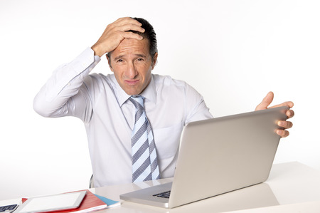 desperate tired senior businessman in crisis working on computer laptop at office desk in stress under pressure facing work problems isolated on white background photo