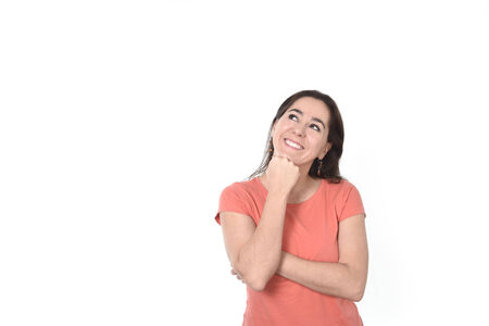 reflexive: sweet beautiful happy Hispanic woman in orange t-shirt thoughtful and pensive thinking and dreaming looking up smiling on copy space isolated on white background Stock Photo
