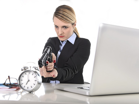 project deadline: young attractive businesswoman furious and angry working with computer laptop pointing gun to alarm clock in out of time, long hours of work and project deadline stress Stock Photo