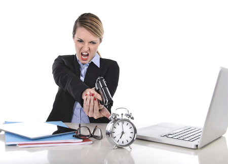 young attractive businesswoman furious and angry working with computer laptop pointing gun to alarm clock in out of time photo