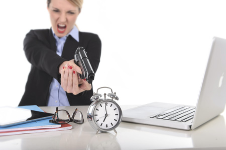 exploited: young attractive businesswoman furious and angry working with computer laptop pointing gun to alarm clock in out of time