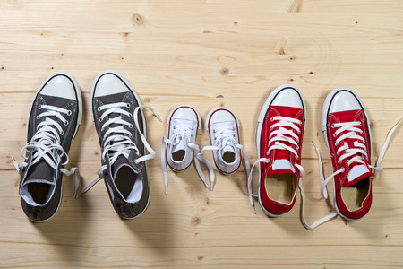 representing: three pair of shoes in father big, mother medium and son or daughter small kid size representing family, growth, education and togetherness concept