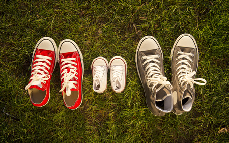 three pair of shoes in father big, mother medium and son or daughter small kid size in grass park with Autumn leaves representing family, growth, education and togetherness concept