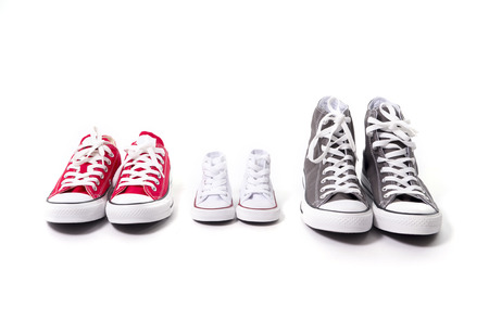 three pair of shoes in father big, mother medium and son or daughter small kid size representing family, growth, education and togetherness concept