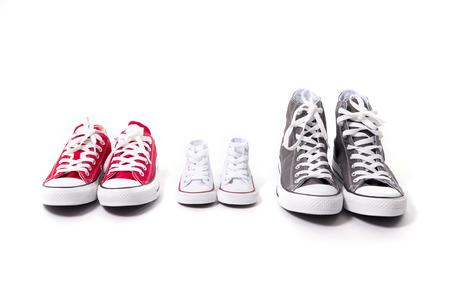 tres pares de zapatos en el padre grande, mediano madre y el hijo o la hija pequeña de tamaño chico que representan la familia, el crecimiento, la educación y el concepto de la unidad