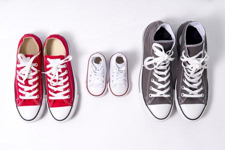 父、母媒体と息子や娘の小さな子供のビッグサイズで家族、成長、教育および一体性の概念を表す靴の 3 つのペア