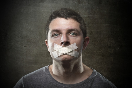 censor: attractive young man with mouth sealed on duct tape to prevent him from speaking keeping him mute and censored in freedom of speech and expression concept