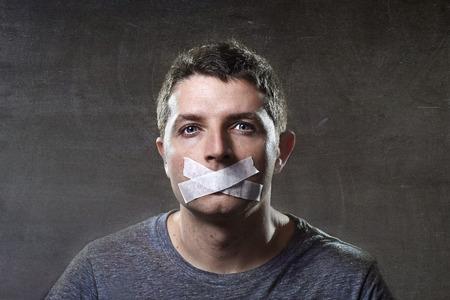 atraktivní mladý muž s ústy zapečetěný na lepicí páskou, aby se zabránilo mu v mluvení udržet ho mute a cenzuroval ve svobodu slova a projevu koncepce