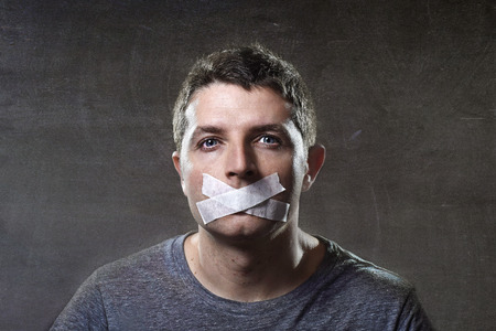 quiet adult: attractive young man with mouth sealed on duct tape to prevent him from speaking keeping him mute and censored in freedom of speech and expression concept