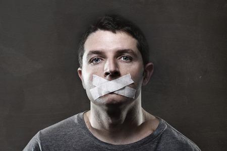Aantrekkelijke jonge man met de mond verzegeld duct tape om hem te beletten te spreken houden van hem mute en gecensureerd in de vrijheid van meningsuiting en expressie-concept Stockfoto - 34681453