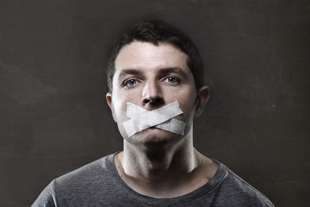 attractive young man with mouth sealed on duct tape to prevent him from speaking keeping him mute and censored in freedom of speech and expression concept