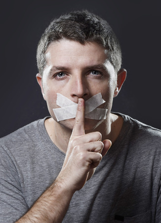 man mouth: attractive young man with mouth sealed on duct tape to prevent him from speaking keeping him mute and censored in freedom of speech and expression concept