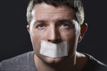 taped: attractive young man with mouth sealed on duct tape to prevent him from speaking keeping him mute and censored in freedom of speech and expression concept
